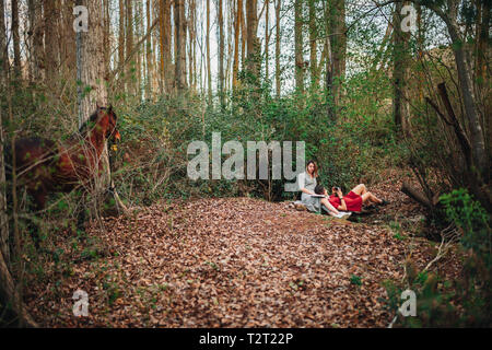 Young couple of women wearing dresses reading a book and taking photos with old camera in the forest with their horse. - Stock Photo