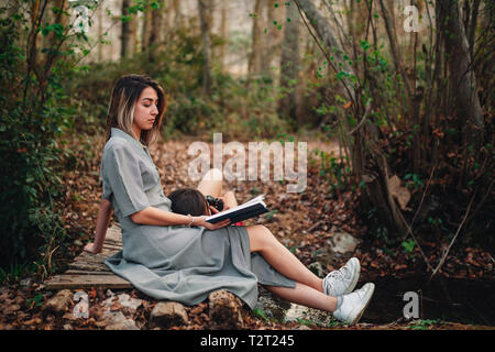Young couple of women wearing dresses reading a book and taking photos with old camera in the forest - Stock Photo