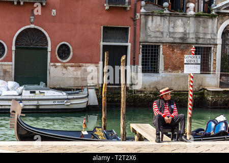 6e3ad1928a7 ... Gondolier dressed in traditional red striped top and straw hat with red  ribbon in Venice