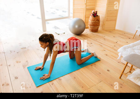 Yoga on mat. Top view of slim woman doing yoga on sport mat near the window in bedroom - Stock Photo