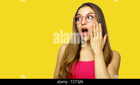 Young woman in glasses looking to the side shocked, studio portrait - Stock Photo