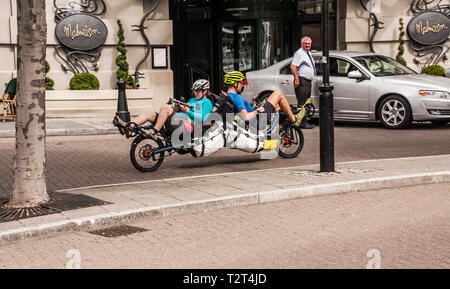 A recumbent back to back tandem cycle in Newcastle with male and female riders on board - Stock Photo