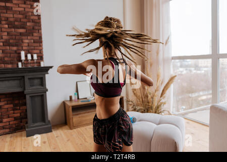 Stretching back. Active woman with nice little braids stretching her back at home near the window - Stock Photo