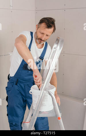 Painter or handyman in denim overalls mixing paint in a tub on an aluminum stepladder in a corner angle with new unpainted wall cladding - Stock Photo