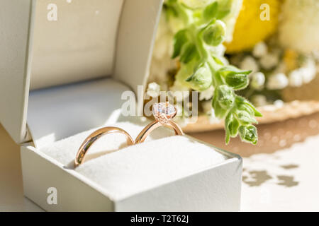 Golden wedding rings in a white box. Flowers on the background. Close up. - Stock Photo