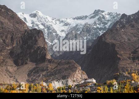 Landscape view of snow capped Ultar Sar mountain in Karakoram range with foliage in autumn in Karimabad. Hunza valley, Gilgit Baltistan, Pakistan. - Stock Photo