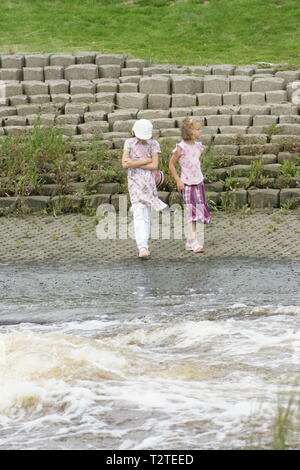 young girls playing near fast moving river, water safety code - Stock Photo