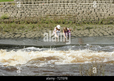 girls playing near open water, water safety, - Stock Photo