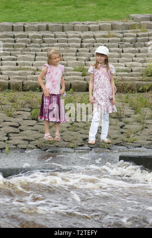 girls playing near fast moving river, water safety, - Stock Photo
