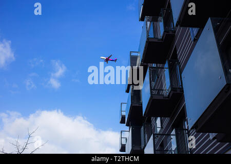 Poznan - Poland / March 16 2019, Plane is flying over new luxury apartment building during one of the last flights, Hungarian budget airlines Wizz Air - Stock Photo