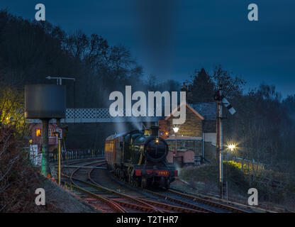 Moody, dramatic, atmospheric, night time capture of vintage UK steam train leaving Highley station on Severn Valley Railway heritage line in the dark. - Stock Photo