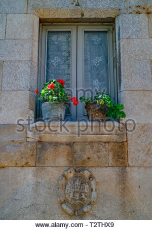 Windows with Red Geraniums in pots on the window ledge of a stone building in Girona, Catalunya, Spain March 2019 - Stock Photo