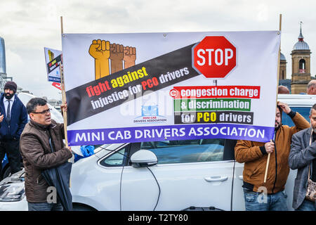 London, UK, 04th April 2019. Minicab drivers block the road on London Bridge protesting against the congestion change on private hire minicabs.  The demonstrators hold and wave flags and placards of UPHD (United Prive Hire Drivers) and IWGB (Independent Workers Union of Great Britain). Credit: Graham Prentice/Alamy Live News - Stock Photo
