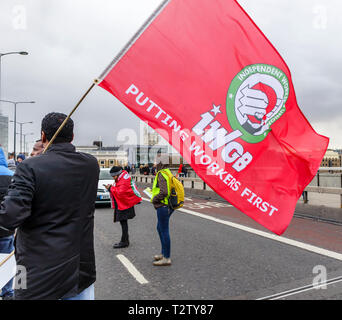 London, UK, 04th April 2019. Minicab drivers block the road on London Bridge protesting against the congestion change on private hire minicabs.  This demonstrators holds and waves the red flag of IWGB (Independent Workers Union of Great Britain). Credit: Graham Prentice/Alamy Live News - Stock Photo
