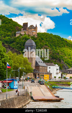 Nice view of the town St. Goarshausen with its ferry landing connected to the main road at the catholic St. Johannes Church on a sunny day with blue... - Stock Photo