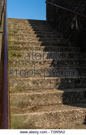 A set of rough concrete steps leading up from the street, half of the steps are in a deep shadow, with a bright blue sky in the background. - Stock Photo