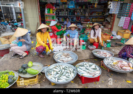 Vietnamese women selling fresh fish, fruit and vegetables outside a grocery store at the street market, Dinh Cau, Phu Quoc island, Vietnam, Asia, - Stock Photo