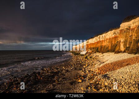 Hunstanton Cliffs at sunset with dark stormy sky, on Norfolk coast, where white chalk overlays red limestone in a colourful formation. England, UK.