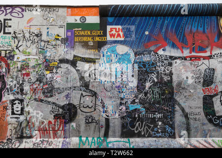 Front view of murals, graffiti, tags and writings at the East Side Gallery, section of the Berlin Wall in Berlin, Germany. - Stock Photo