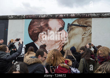 Tourists at the 'My God, Help Me to Survive This Deadly Love' (or 'Fraternal Kiss') mural painting by Dmitri Vrubel at the East Side Gallery in Berlin - Stock Photo