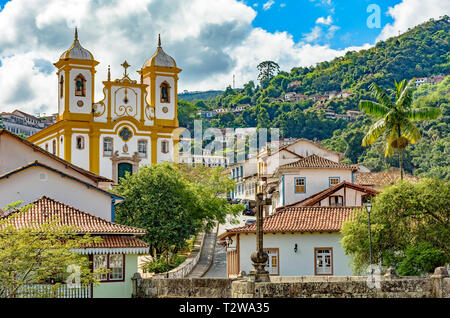 Top view of the center of the historic Ouro Preto city in Minas Gerais, Brazil with its famous churches and old buildings with hills in background - Stock Photo