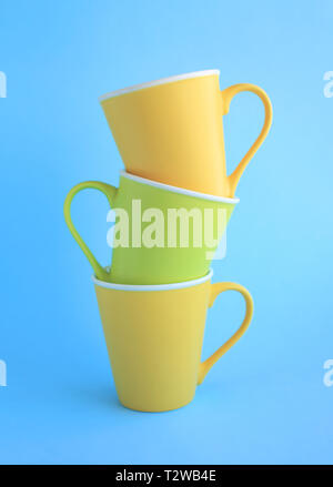 Three colorful yellow and light green ceramic cups on light blue background. - Stock Photo