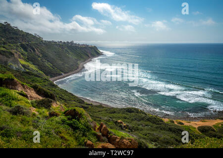 Scenic coastal view of tall cliffs of Bluff Cove covered with vegetation on a sunny spring day with  turquoise colored water and rocky beach, Blufftop - Stock Photo