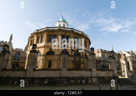 A row of stone sculptured heads mounted on the railings and gate at the Sheldonian Theatre in Broad Street, Oxford, Britain - Stock Photo