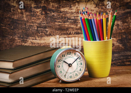 Colored pencils in a glass next to books and watche. Education concept. On a wooden background - Stock Photo