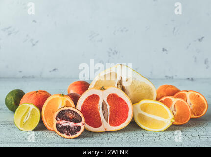 Variety of citrus fruit on the wooden background - Stock Photo