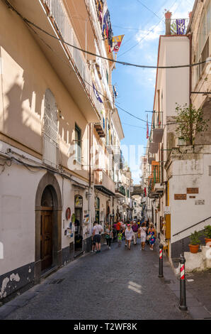 Tourists and holiday makers walking down a narrow street in Amalfi, Italy - Stock Photo