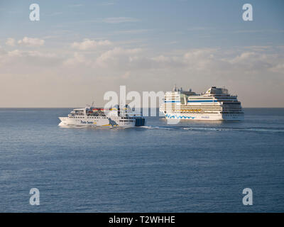 The Porto Santo Island Ferry and AIDA Stella cruise ship leaving Funchal port in Madeira after sunrise on a clear morning. - Stock Photo