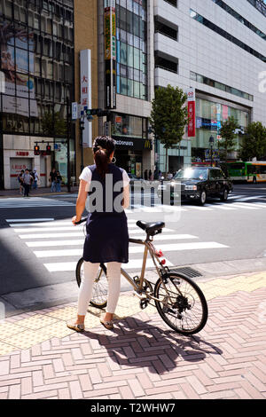 Pictured is going to bake waiting to cross the road Tokyo Japan. - Stock Photo