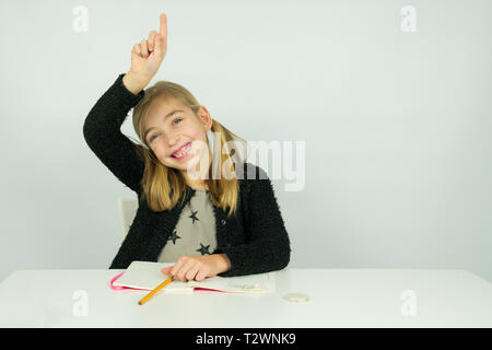 Cute girl is raising her hand in the classroom. She knows the answer the teacher asked - Stock Photo