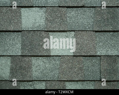 closeup of modern roof trapezoid square shingles tiles in gray color. waterproof scabrous rough surface for house exterior cover - Stock Photo