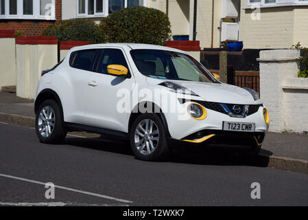 White Nissan Juke with yellow optional detailing parked in a residential street. Personalised special number plate. SUV crossover built in UK. NMUK - Stock Photo
