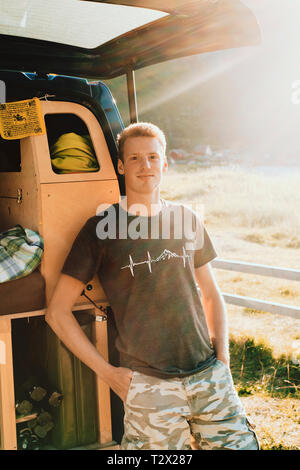 A location lifestyle portrait of a young millennial van life instagrammer living and traveling in his self build camper van. - Stock Photo