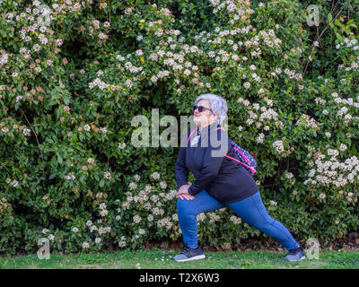 A senior woman with white hair practicing gymnastics in an urban park - Stock Photo