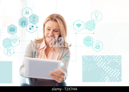 smiling pretty woman with blonde hair using digital tablet, smart home concept - Stock Photo