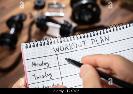 Close-up Of A Human's Hand Writing Workout Plan On Diary In The Gym - Stock Photo
