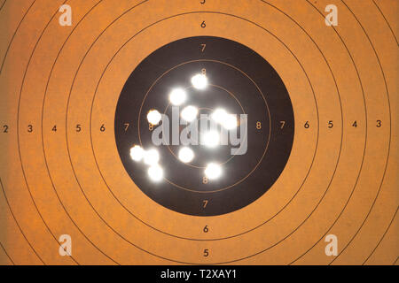 Close up of a shooting target with backlit bullet holes - Stock Photo