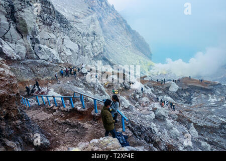 View of the Kawah Ijen crater with tourists and sulfur miners climbing up the slope and toxic sulfuric gases emeging from the lake. Java, Indonesia. - Stock Photo