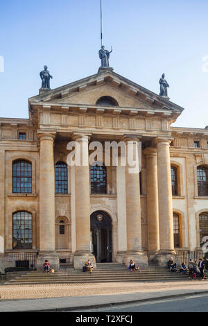 Tourists and students sit on the steps of the early 18th Century Clarendon Building in Broad Street, Oxford - Stock Photo