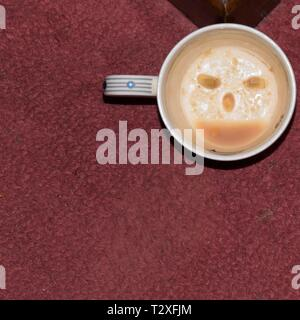 A white cup, on a carpet, with a smiley face designed with lemon pip eyes and coffee dregs mouth. Fun to amuse children and folk in a festive mood. - Stock Photo
