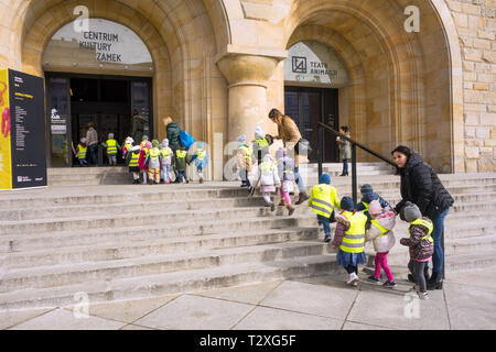 Young school children boys and girls wearing high vis jackets and clothing being led in a crocodile by teachers into the theater in Poznan Poland - Stock Photo
