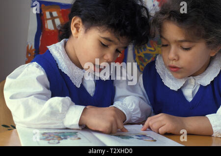 two little girls reading out loud in class - Stock Photo