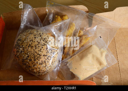 chicken burger set meal in plastic packaging in paper box - Stock Photo