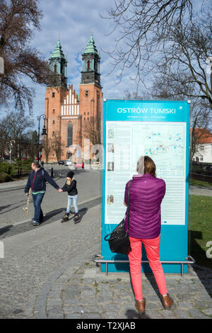 Woman reading the information board outside the cathedral on Ostrow Tumski Island,  in the Polish city of Poznan Poland - Stock Photo