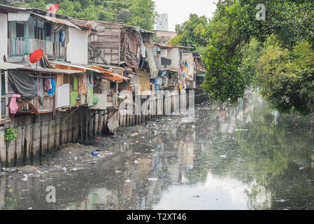 Bangkok, Thailand - September 25, 2018: slums along a smelly canal (Khlong Toei) full of mud and garbage in Khlong Toei District. - Stock Photo