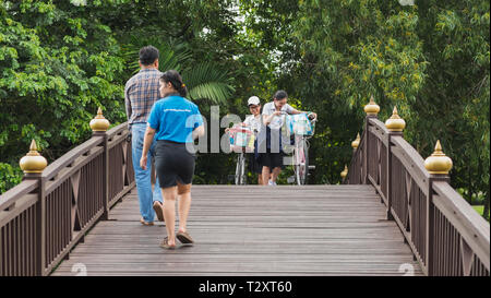 Bangkok, Thailand - September 25, 2018: smiling Thai girls with bicycles walk over a wooden bridge towards other passersby in a park in Bang Krachao. - Stock Photo